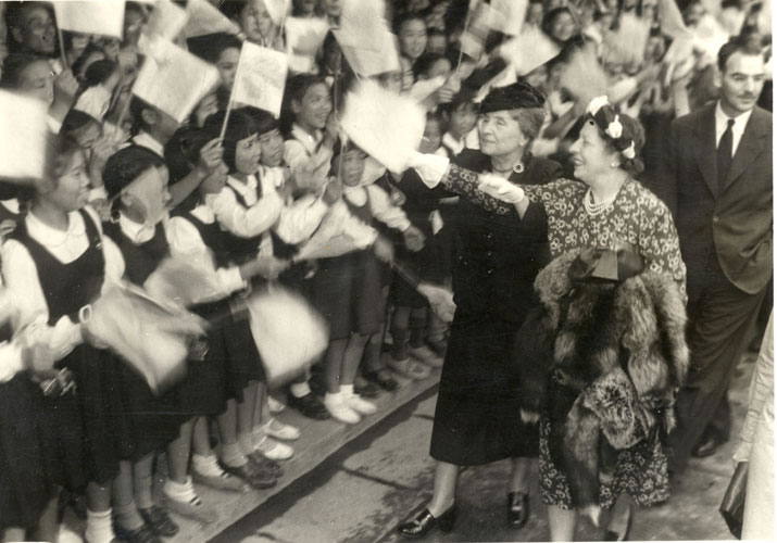 Photo of Helen Keller and Polly Thomson being greeted by a crowd of young girls, Kobe Japan, 1948.