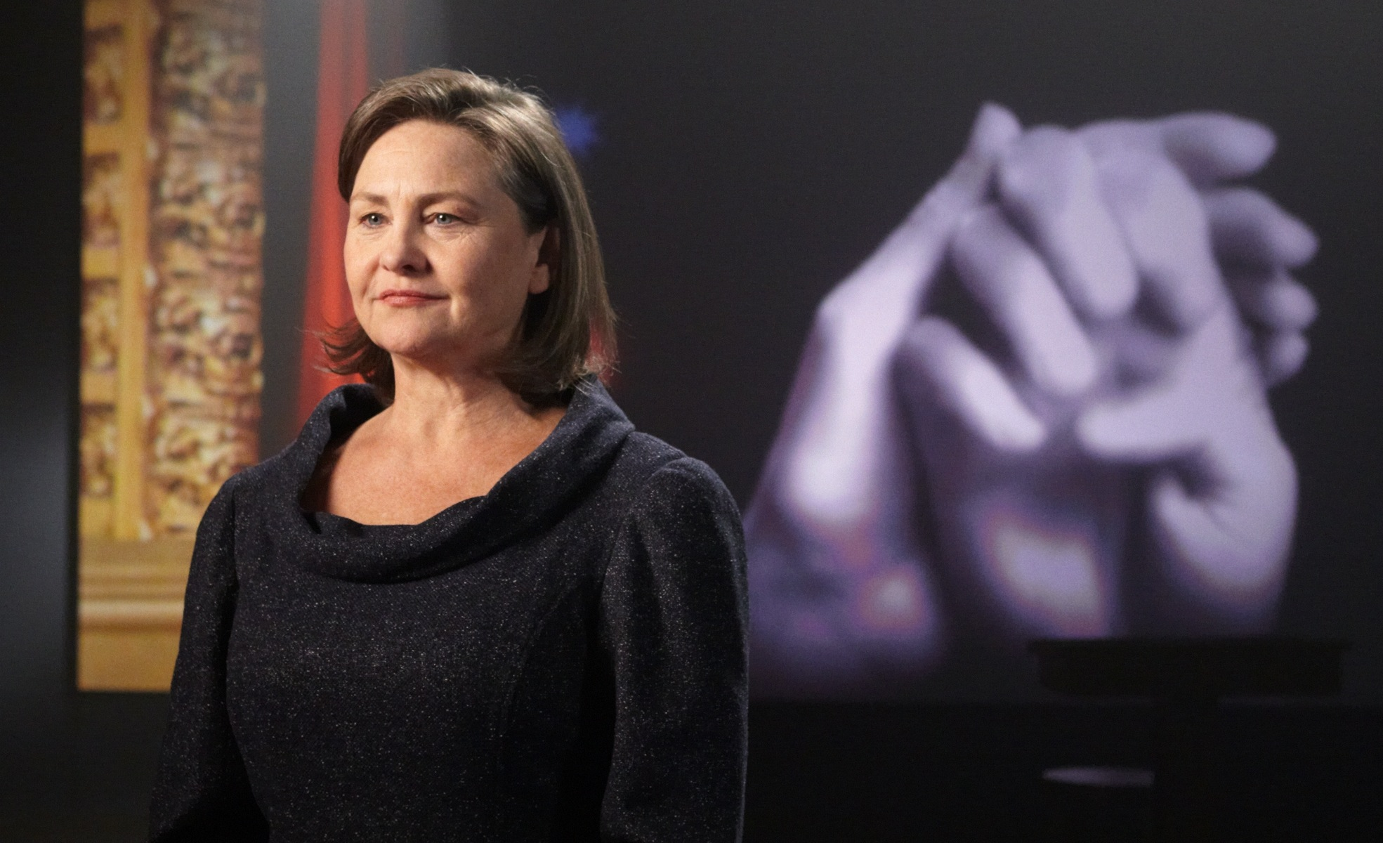 Cherry Jones on the Becoming Helen Keller set, with hands spelling a word in the background.
