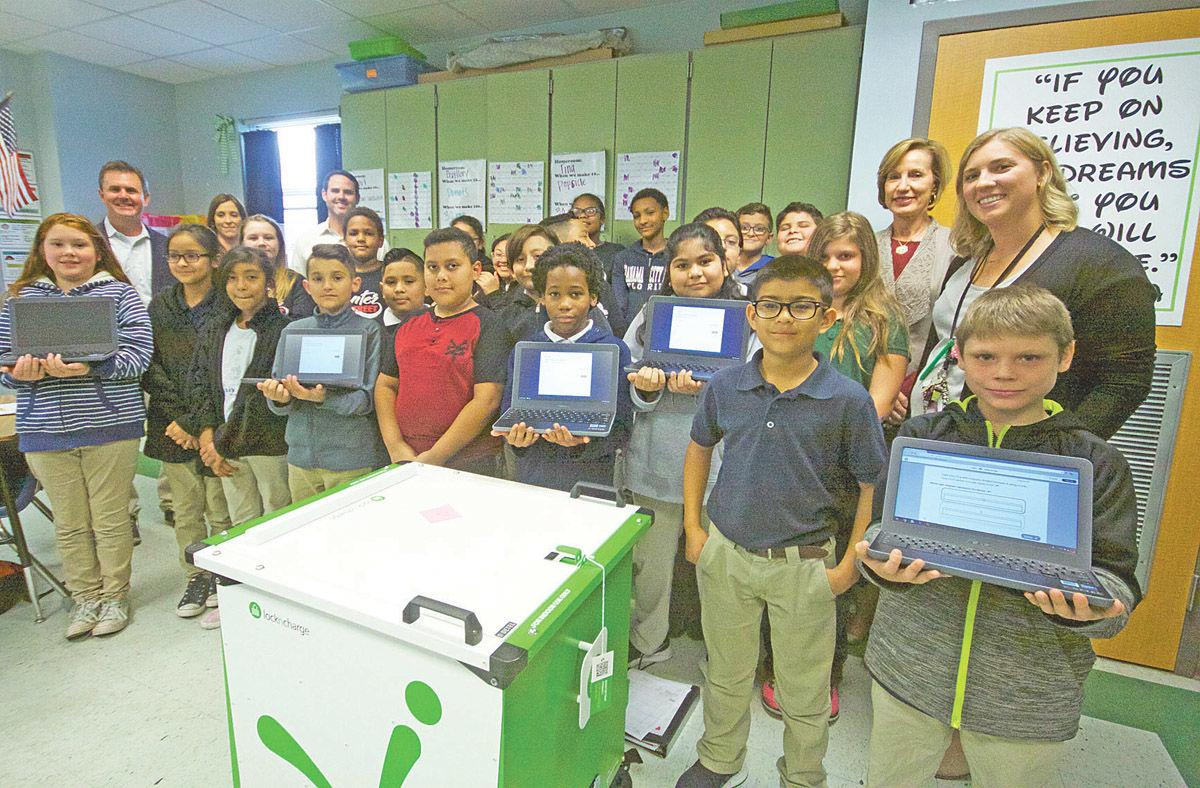 Students show off the new Chromebook computers they will use in their math class at Center Street Elementary School Thursday afternoon.
