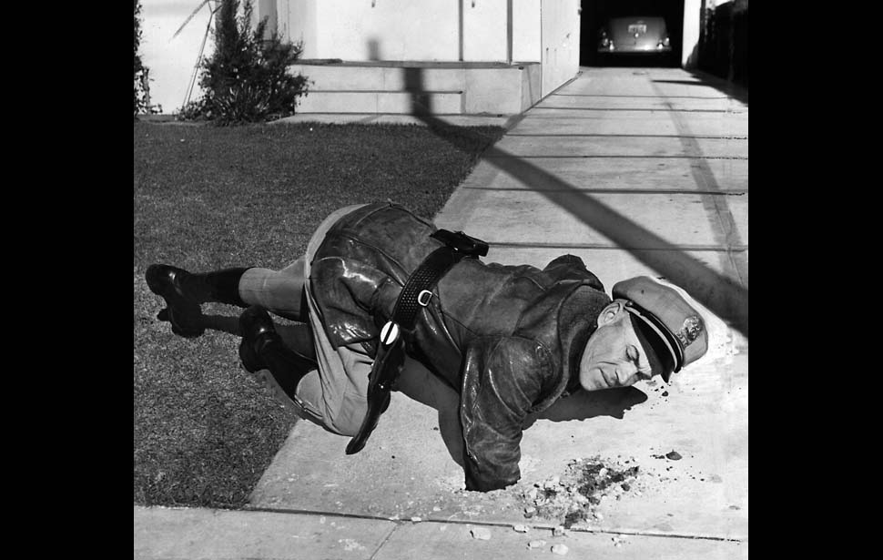 A police officer reaching into a hole caused by a dud that fell in Santa Monica, via the  Los Angeles Times