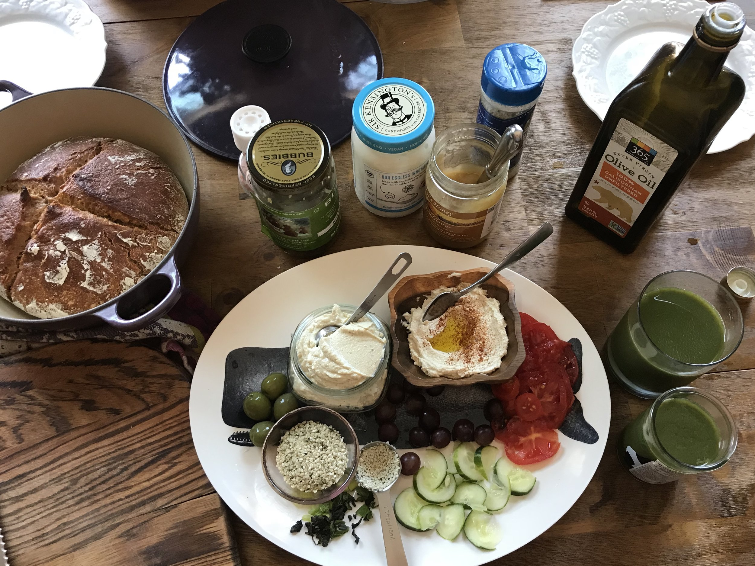Lunch board with hummus, veggies, fresh sourdough, and all the toppings