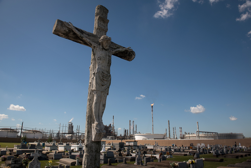 A crucifix stands in the Holy Rosary Cemetery in Killona, La., as the Dow Chemical Plant looms in the background.