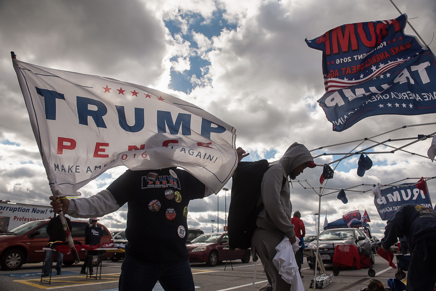 "Andy Stafford, a vendor from Sarasota, Florida, holds a Trump flag as he sets up his stand in the parking lot of the International Exposition Center prior to a campaign stop by Republican presidential nominee Donald Trump on October 22, 2016 in Cleveland, Ohio. ""I'm a Trump lover,"" says Stafford."