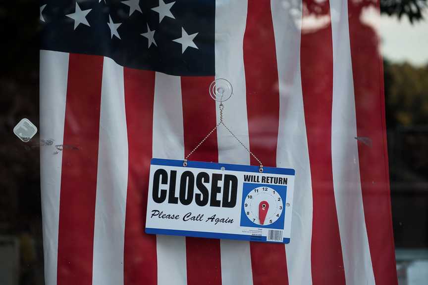 A closed sign hangs in front of a flag in a storefront in East Liverpool, Ohio on Thursday, Sept. 15, 2016.