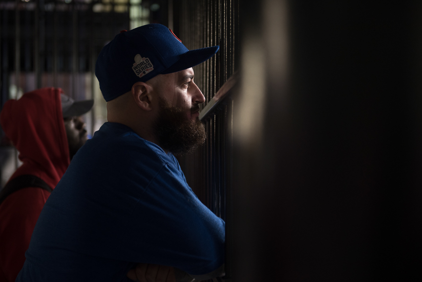 Stephen Caton, 29, of St. Louis, a Chicago Cub fan watches game 6 of the World Series through a fence at Progressive Field on November 1, 2016 in Cleveland, Ohio.