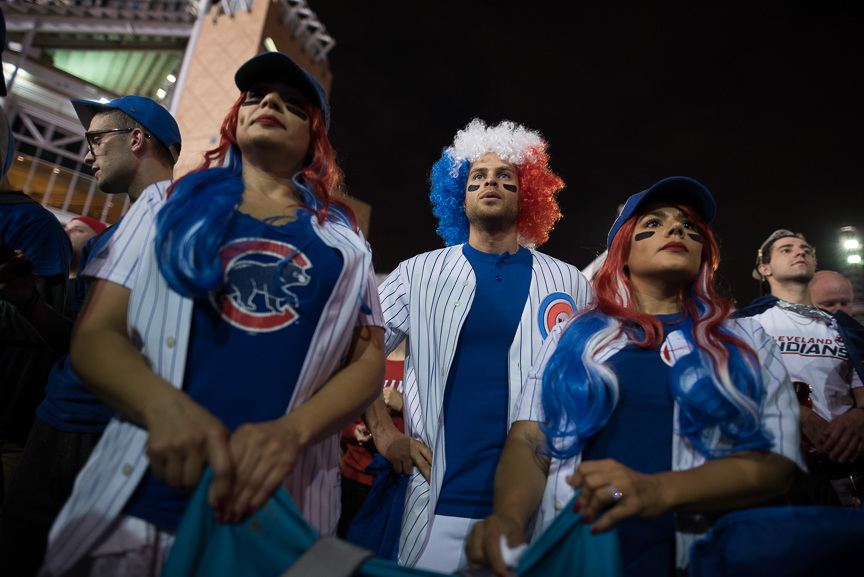 (L-R) Dayana Guzman, 38, Alex Marquez, 33, and Doraliz Guzman-Marquez, 35, all of Chicago cheer for the Cubs in outside of Progressive Field during game 7 of the World Series between the Cleveland Indians and the Chicago Cubs on November 2, 2016 in Cleveland, Ohio.