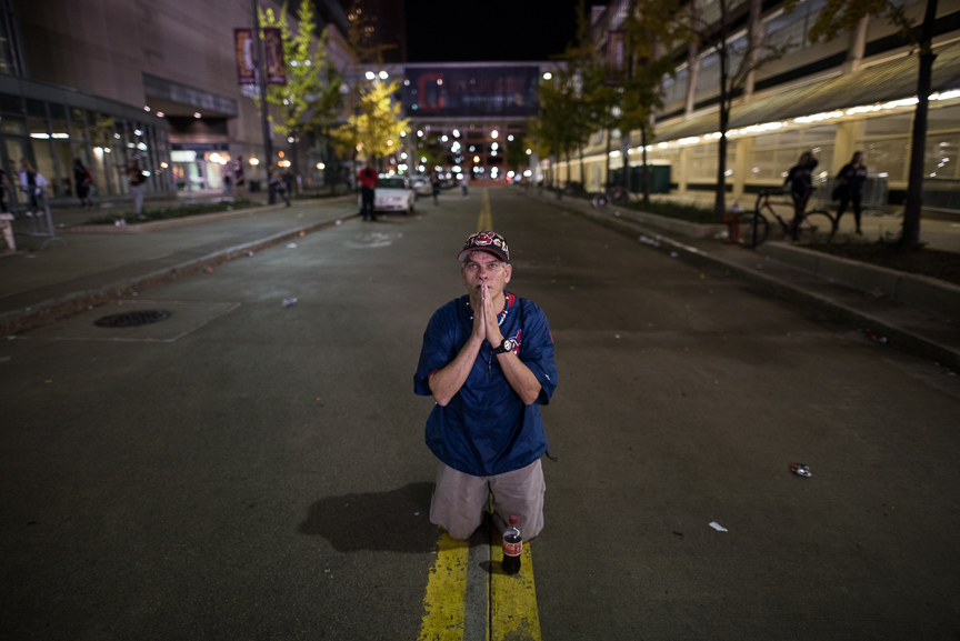 William Burgos of Cleveland prays in the street outside of Progressive Field during the 9th inning of game 7 of the World Series between the Cleveland Indians and the Chicago Cubs on November 2, 2016 in Cleveland, Ohio.