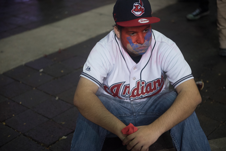 An Indian fan sits in the street after the Chicago Cubs defeated the Cleveland Indians 8-7 in game 7 of the World Series on November 3, 2016 in Cleveland, Ohio.