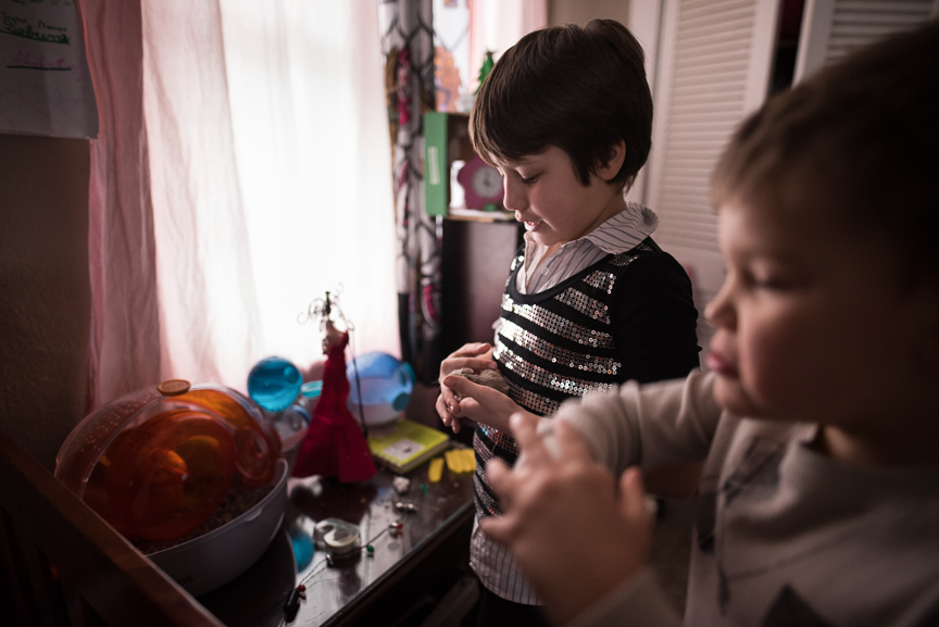 Sabrina Snyder, 9, coaxes her hamster out of its cage in the bedroom of her Brookline home as her bother, Miles, 5, stands by on Monday, January 30, 2017. Sabrina was mauled by a Rottweiler in Aug. 2014, leaving her with several physical injuries as well as emotional scars from the incident.