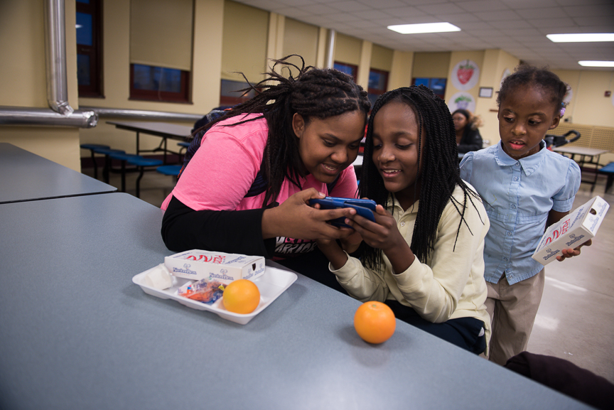 Monet Spencer looks at a game with Tya Carter, 10, as Aminyah Dooley, 5, looks on after an after-school tutoring session at Pittsburgh Miller PreK-5. Spencer earns about $100 every two weeks from the tutoring job. She pays $50 a month in rent.