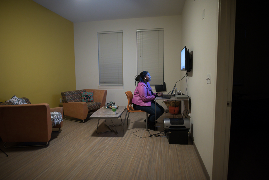 """This is Monet Spencer's home. Here, she's looking through videos on her computer. She uses her phone to connect to the Internet through a hotspot. Spencer and her twin brother were considered homeless after their mother died. Spencer eventually acquired an apartment through ACTION-Housing's MyPlace Youth program. """"It was the happiest day of my life,"""" Spencer says about getting her own apartment."""