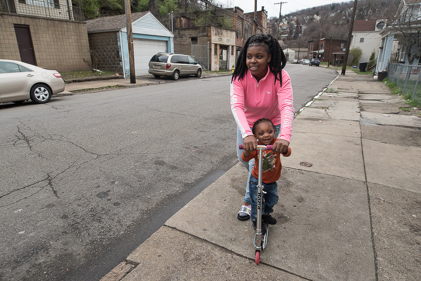 Dezmaire Baker, 17, helps her son, Dorian, 2, to ride a scooter along the sidewalk in front of their Braddock home on April 3, 2017.