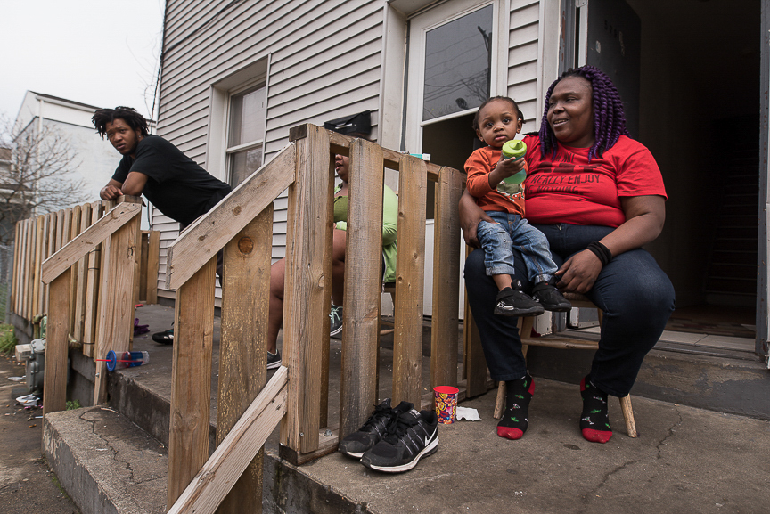Ronnika Baker, 36, holds her grandson, Dorian, 2, as she sits on the porch of their Braddock home on April 3, 2017.