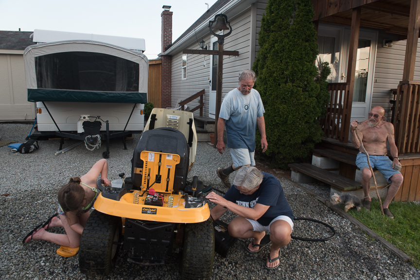 """George Barron, 78, right, watches as Barry Custer, 64, cleans his lawn tractor with his wife, Robbie, 62, and granddaughter Emma Grigg, 7, at his home on May 18, 2017 in Acosta, Pa. """"If they put coal miners back to work that be great,"""" Custer, a coal miner with AK Coal Resources, says speaking of the opening of Corsa Coal's new Acosta Deep Mine. """"This town was built on coal,"""" he continues, having worked as a coal miner since he was 18. Custer's wife, Robbie's cousin Mark Popernack was one of the 9 miners rescued from the Quecreek Mine in 2002.  Justin Merriman  for The Wall Street Journal"""