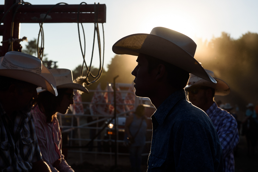 A cowboy stands in the back pens behind the chutes as the sun sets at the Fort Armstrong Professional Rodeo on Saturday, July 8, 2017 in Ford City, Pa.
