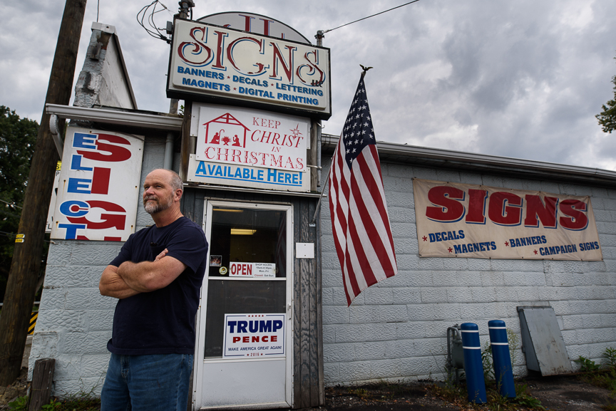Leon Moyer, 60, owner of JL Signs stands in front of his business on Thursday, Aug. 25, 2017 in Ruffs Dale, Pa. Moyer has continued to make and sale pro-Trump signs and bumper stickers long after the election has passed. 