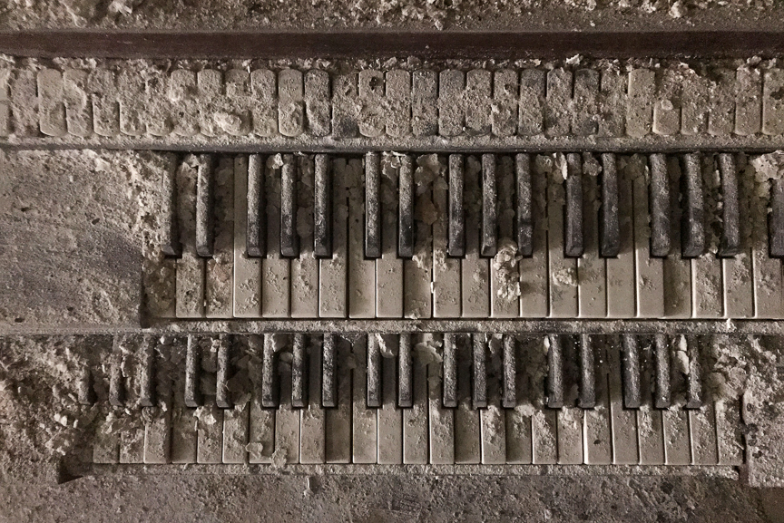 An organ sits inside of an abandoned Pittsburgh church covered by years of dust and dirt.