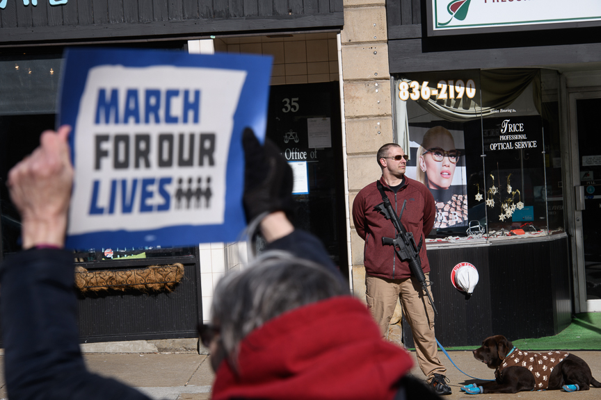 Kristine Hayes of Greensburg, Pa., holds up a 'March for Our Lives' sign as Martin Palla, 33, of Rostraver Township, Pa., stands with his AR-15 rifle across the street from demonstrators joining in the 'March for Our Lives' rally at the Westmoreland County Courthouse on Friday, March 23, 2018 in Greensburg, Pa. 