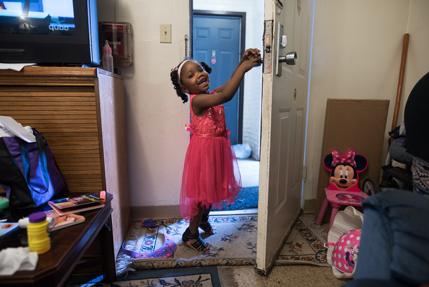 Trinity Glenn, 3, stands in the doorway of her grandmother's living room.