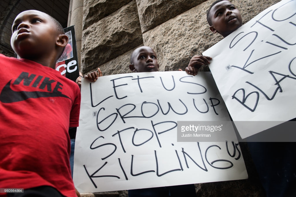 Lorde Watkins, 6, left, and his brothers, Legend, 9, center, and Maceo, 10, right, join over 200 people gathered for a rally to protest the fatal shooting of an unarmed black teen at the Allegheny County Courthouse on June 21, 2018 in Pittsburgh, Pennsylvania. Antwon Rose, 17, was killed by an East Pittsburgh police officer Tuesday night when the he ran after police stopped a vehicle he was in that was suspected to be involved in an earlier shooting. The organizers of the rally called on Allegheny County District Attorney Stephen Zappala Jr. to bring criminal charges against the officer who fatally shot Rose. (Photo by Justin Merriman/Getty Images)
