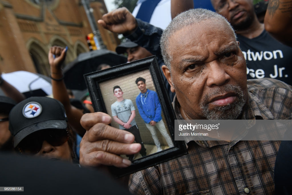 A man holds a photo of Antwon Rose as he joins a protest for the police shooting of Rose during a Juneteenth celebration on June 23, 2018 in Pittsburgh, Pennsylvania. Rose, an unarmed black teenager, was shot Tuesday night, leading to protests and outraged across the city. (Photo by Justin Merriman/Getty Images)