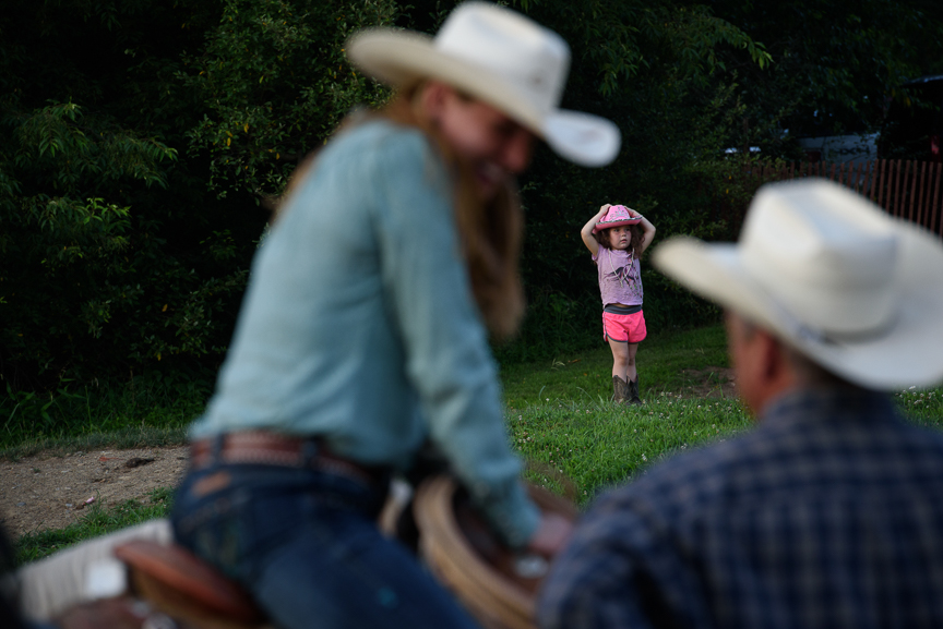 Beth Haifley, 5, of Baltimore, Md., watches competitors talk at the Fort Armstrong Championship Rodeo on Friday, July 13, 2018 at the Crooked Creek Horse Park in Ford City, Pa.
