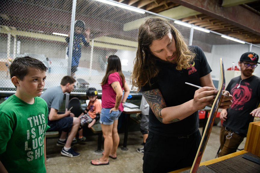 Kerry Weber, 37, owner of Switch and Signal Skatepark, helps set up a new skateboard for Casey Byrne, 10, on Sept. 1, 2018 in Swissvale, Pa.