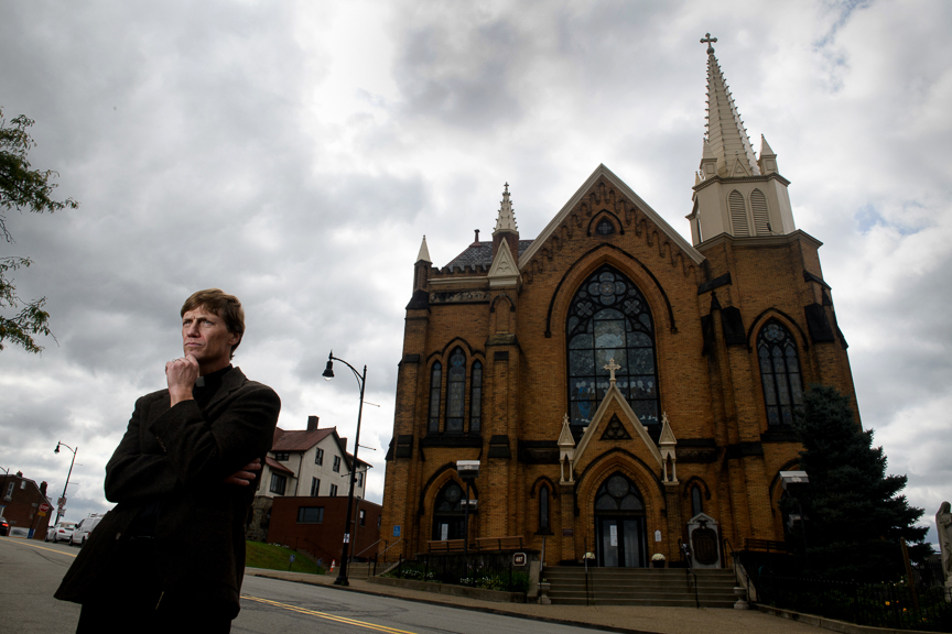 The Rev Michael Stumpf stands outside of St Mary of the Mount Church on Friday, October 12, 2018 in Pittsburgh, Pa. Stumpf has found it 'deeply painful' to be confronted by angry and suspicious parishioners. But it was also appropriate, he said.