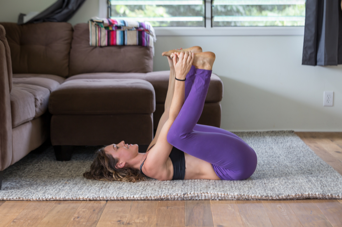 Dead bug pose. If it's too hard to grab your feet grab the back of your thighs instead