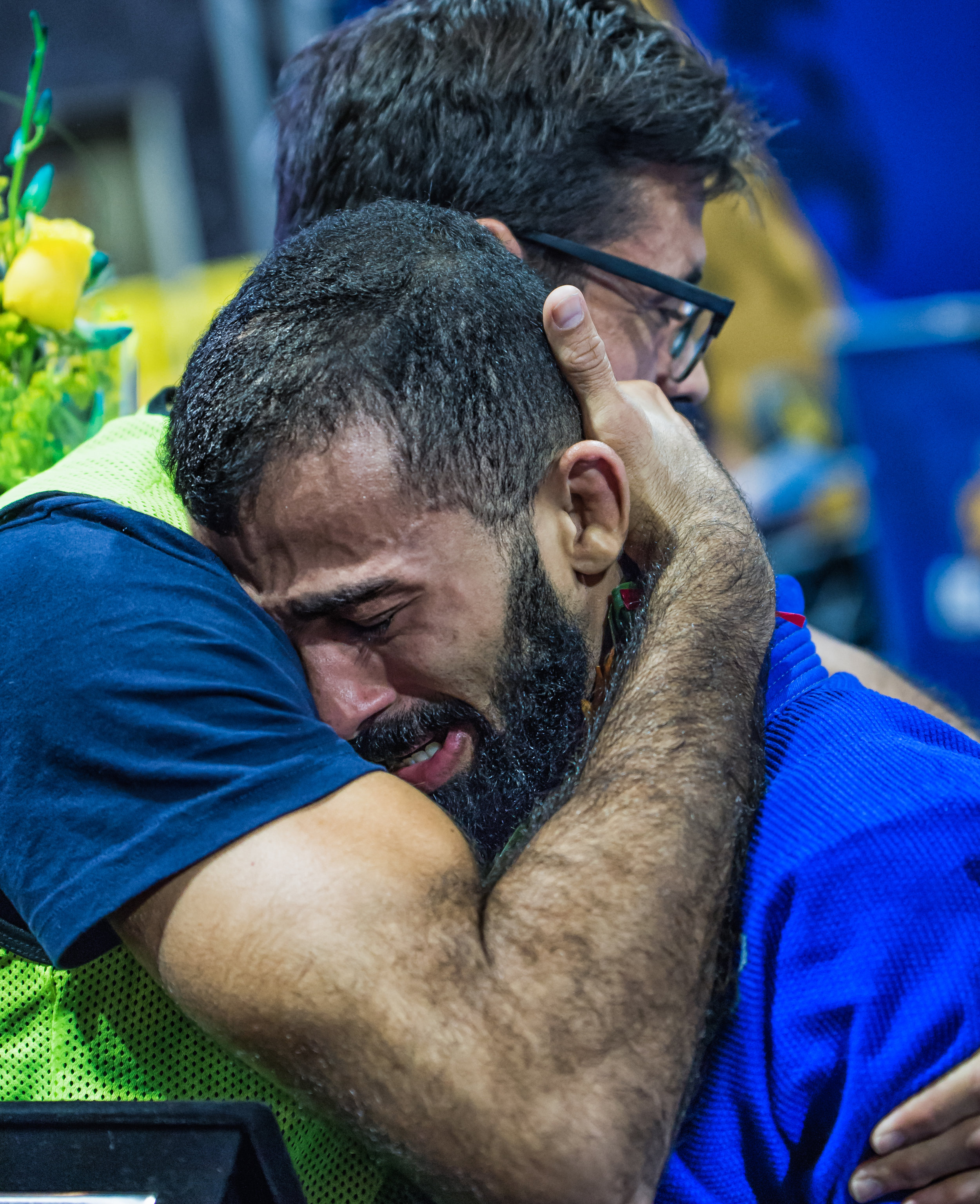 Bruno Malfacine falls into the embrace of his coach, Mario Reis after stepping off the top of the podium for a record 10th time.