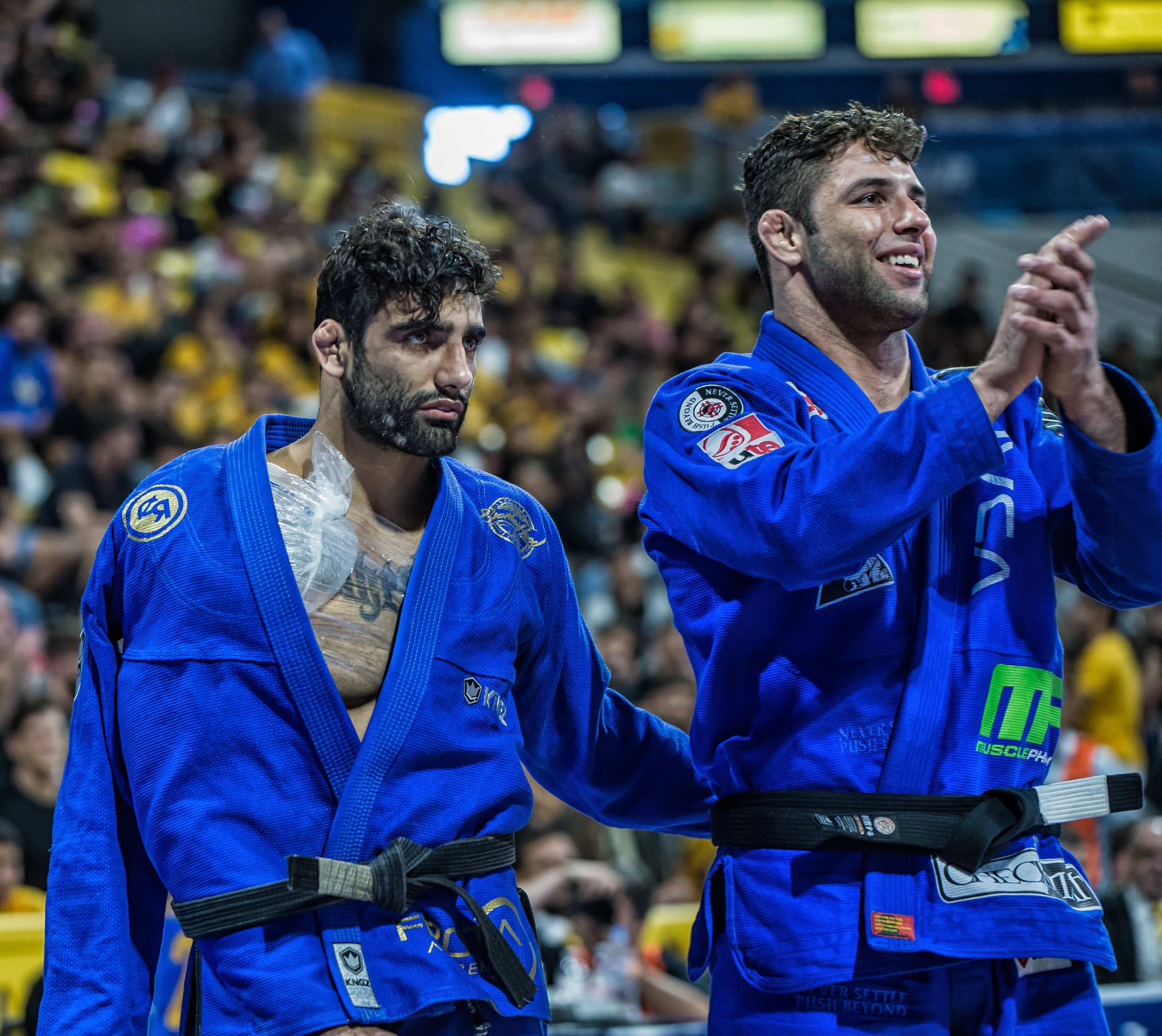 "This photo is immediately after Marcus ""Buchecha"" Almeida bequeathed his 6th Absolute Gold Medal to his friend, Leandro Lo, who was injured during his Super Heavy Finals match vs. Mahamed Aly. Lo was unable to compete for the Absolute Final, and Buchecha shocked the crowd, and Lo, when the referee raised Lo's hand to signal he would go home with the Absolute Gold."