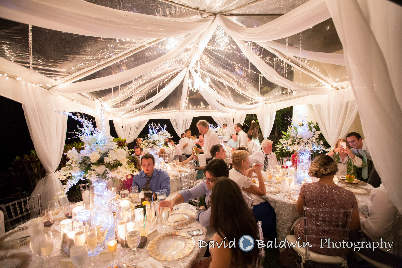 "Clear Chiavari chairs with ivory cushions with 20' wide clear tent, sheer fabric leg drapes, twinkle lighting, chandelier and 66"" round tables for wedding at Hale Wailele in Keauhou.      Event  Outrageous Gourmet   