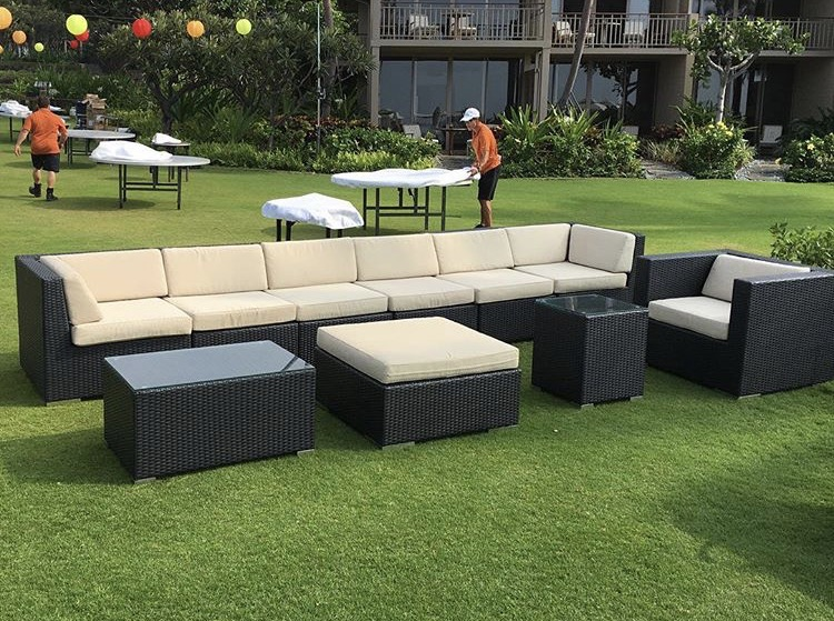 Black Wicker Sectional with an Arm Chair, Coffee Table, Ottoman, and End Table.