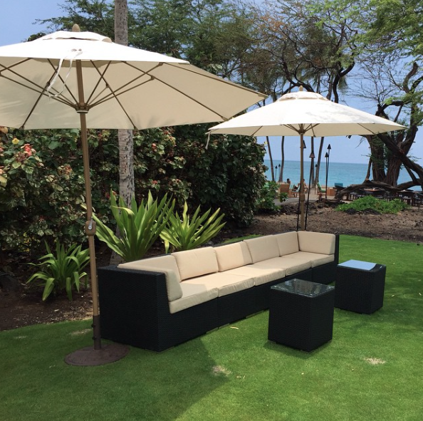 Black Wicker Sectional accompanied by two End Tables, and two Market Umbrellas.
