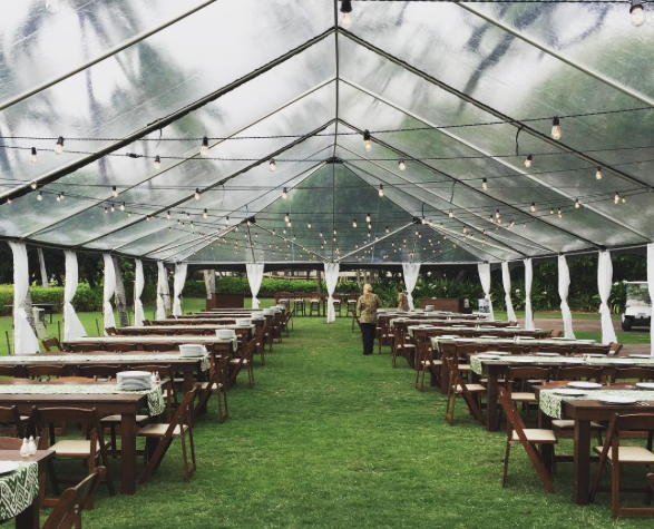 40x clear tent with thin white leg drapes, dark wood farm tables, dark wood padded folding chairs, and bistro lighting for wedding at  Mauna Kea beach  south point lawn. Coordinated by  Bliss in Bloom
