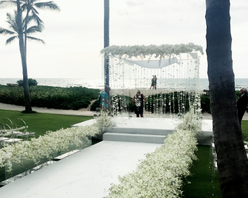 Custom white walkway and staging with white carpeting for ceremony at  Four Seasons Hualalai  palm grove.  Flowers  Grace Flowers Hawaii