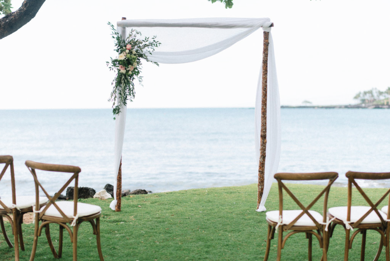 Vineyard Cross Back Chairs for an ocean front ceremony. Coordination  Bliss in Bloom  I Photo  Sarah Goss Photography