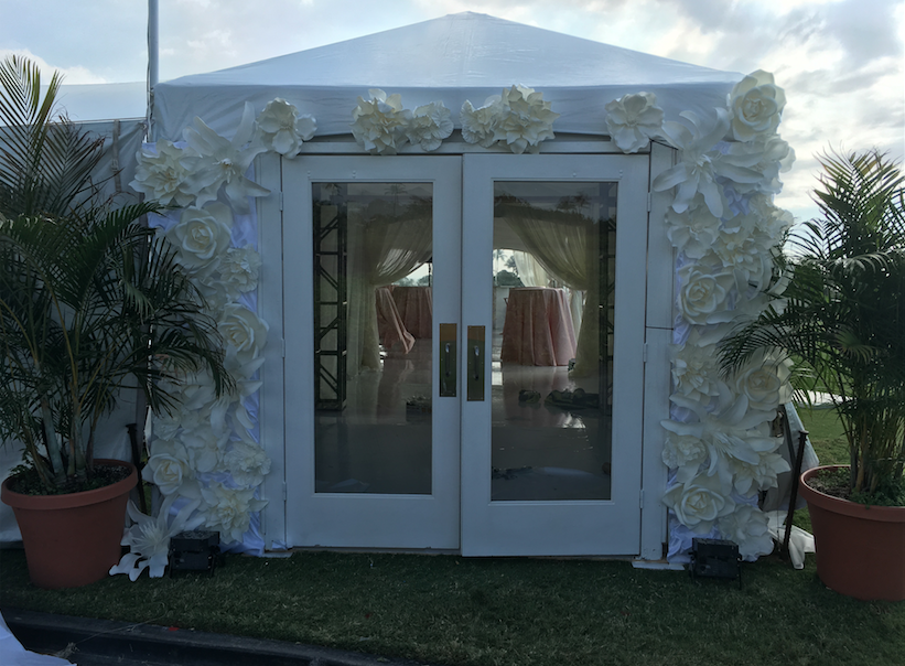 Palm fronds and flower wall framing a tent door from  Production Hawaii