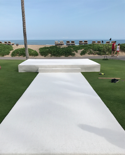 Custom white walkway and staging with white carpeting for ceremony at  Four Seasons Hualalai  palm grove.