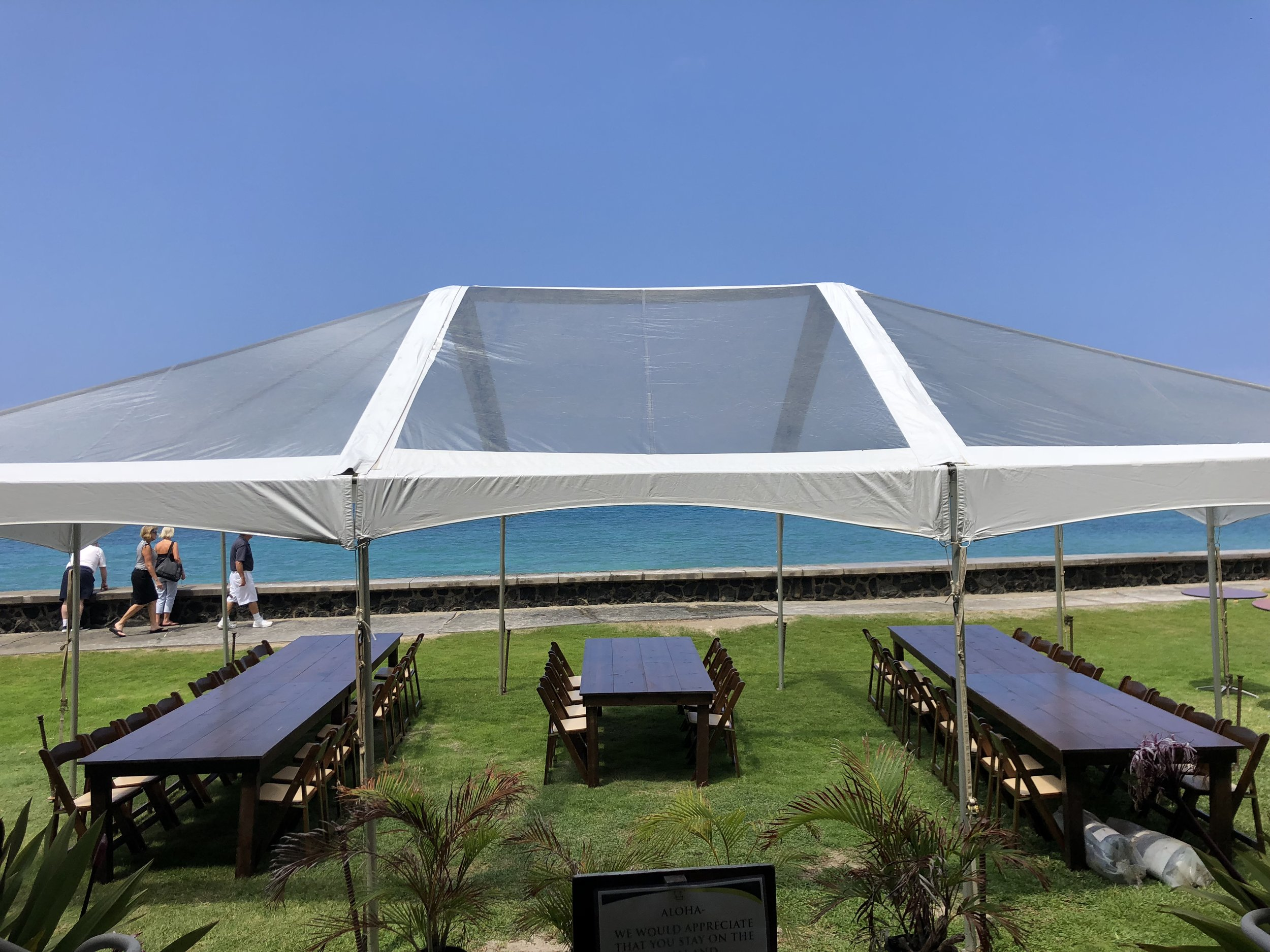 20x clear tent at Hulihee Palace (ocean side), with dark wood farm tables and dark wood padded folding chairs.