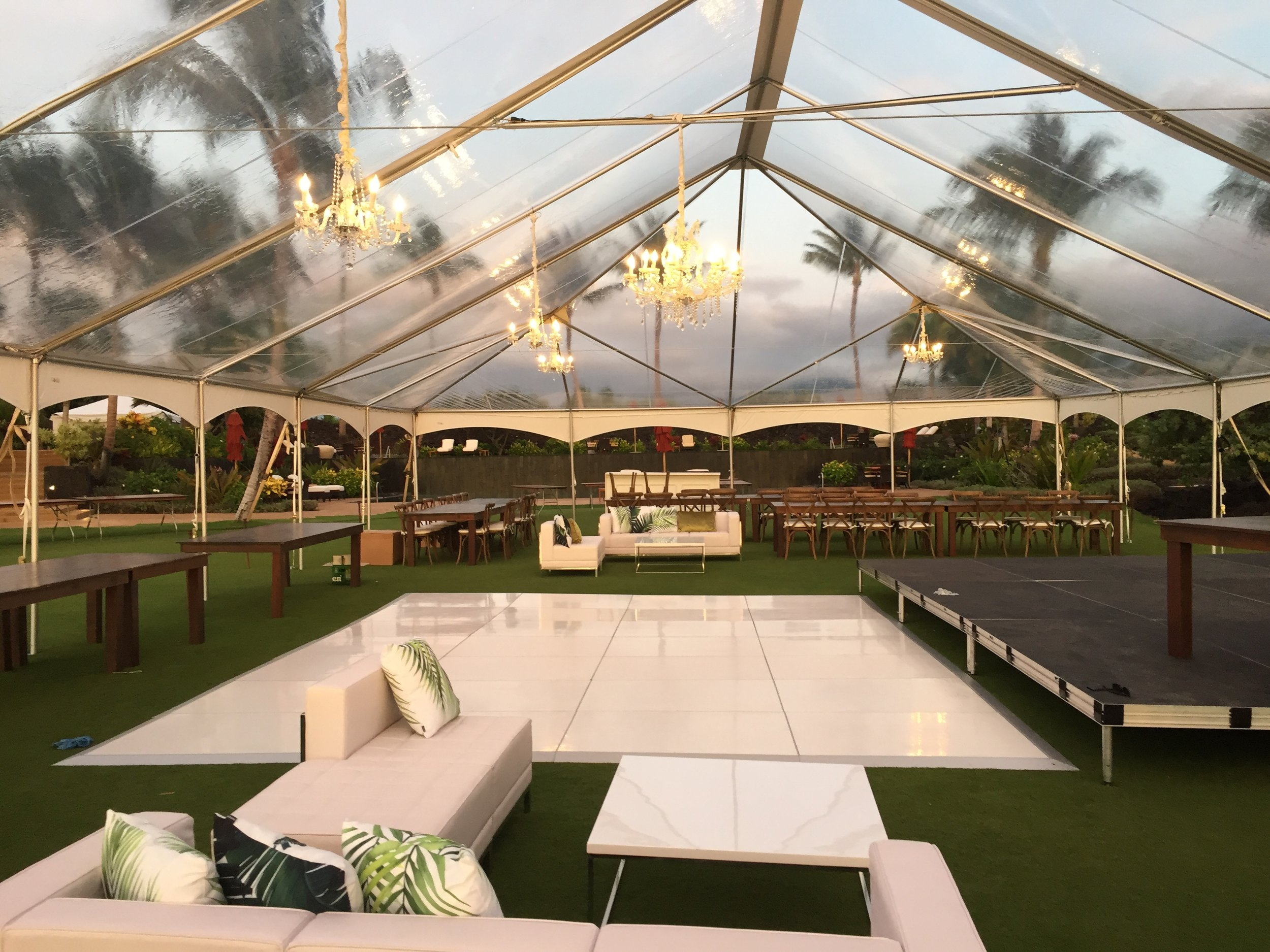 40x80 clear tent with white trim for wedding at Kukio North development. Featured in People Magazine. With Dark wood farm tables, crossback vineyard chairs, high gloss white dance floor, staging, chandeliers, and white leather lounge furniture.