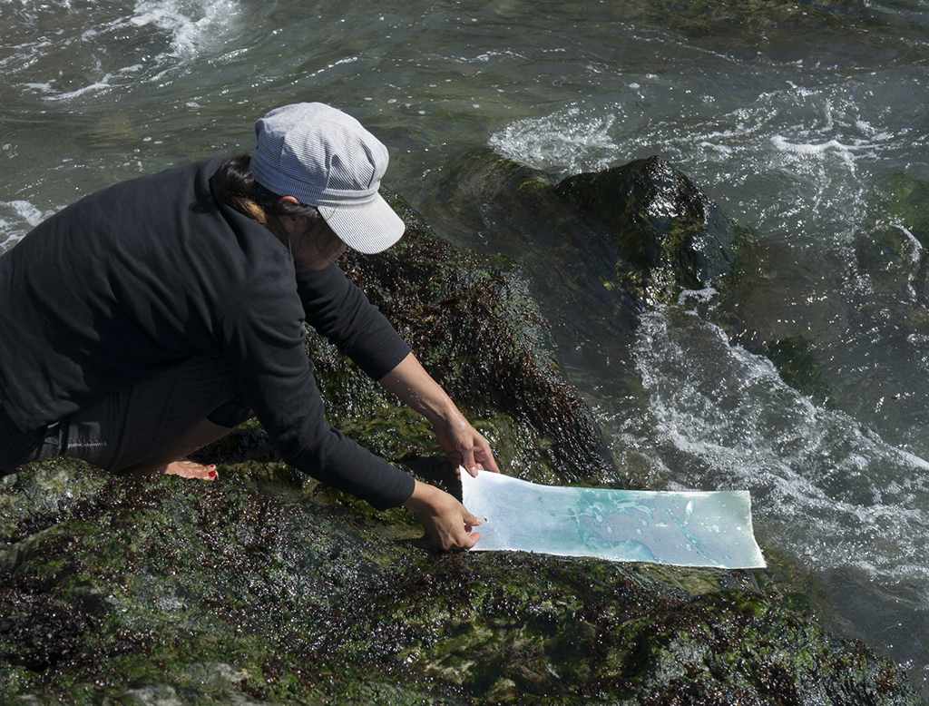 Tomiko processing cyanotype in the ocean.