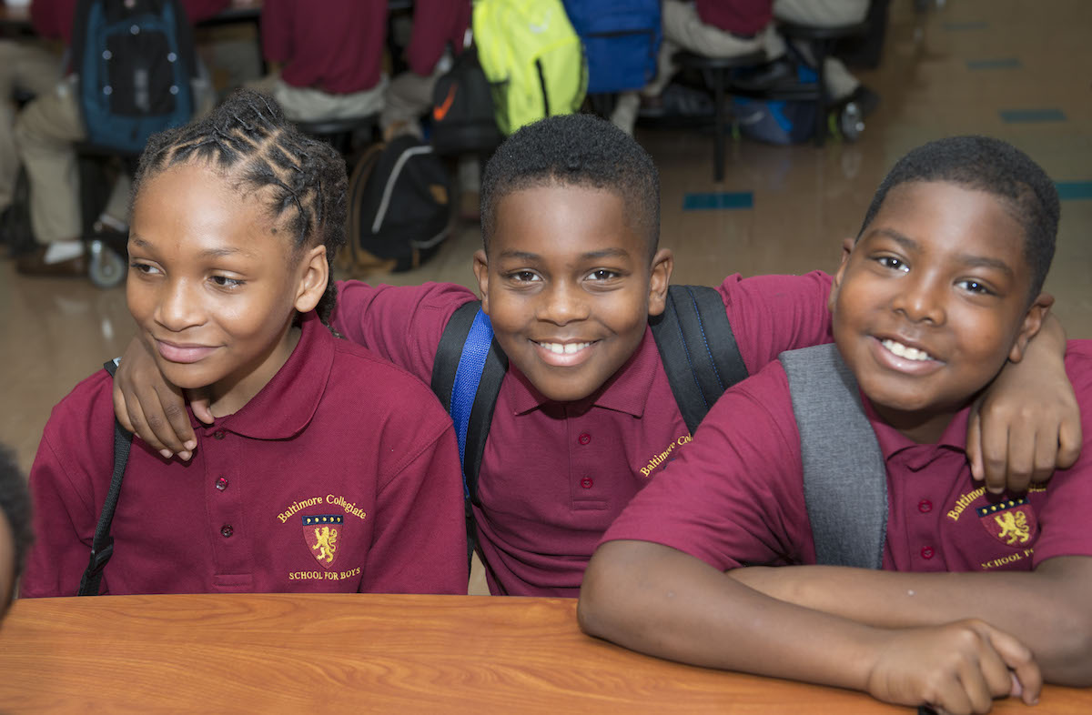 boys smile for photo in lunch room at school