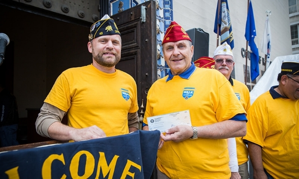 Hollywood Post 43 2nd Vice Commander Michael Hjelmstad presents a donation check to American Legion National Commander Charles E. Schmidt for his fundraising project during Post 43's Walk for Veterans Dec. 11, 2016. (Photo by Jon Endow/The American Legion)