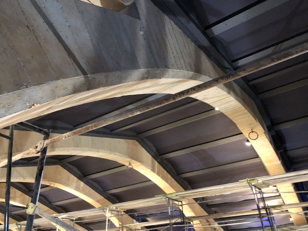 Original concrete texture in the arches and acoustically treated ceiling are featured.