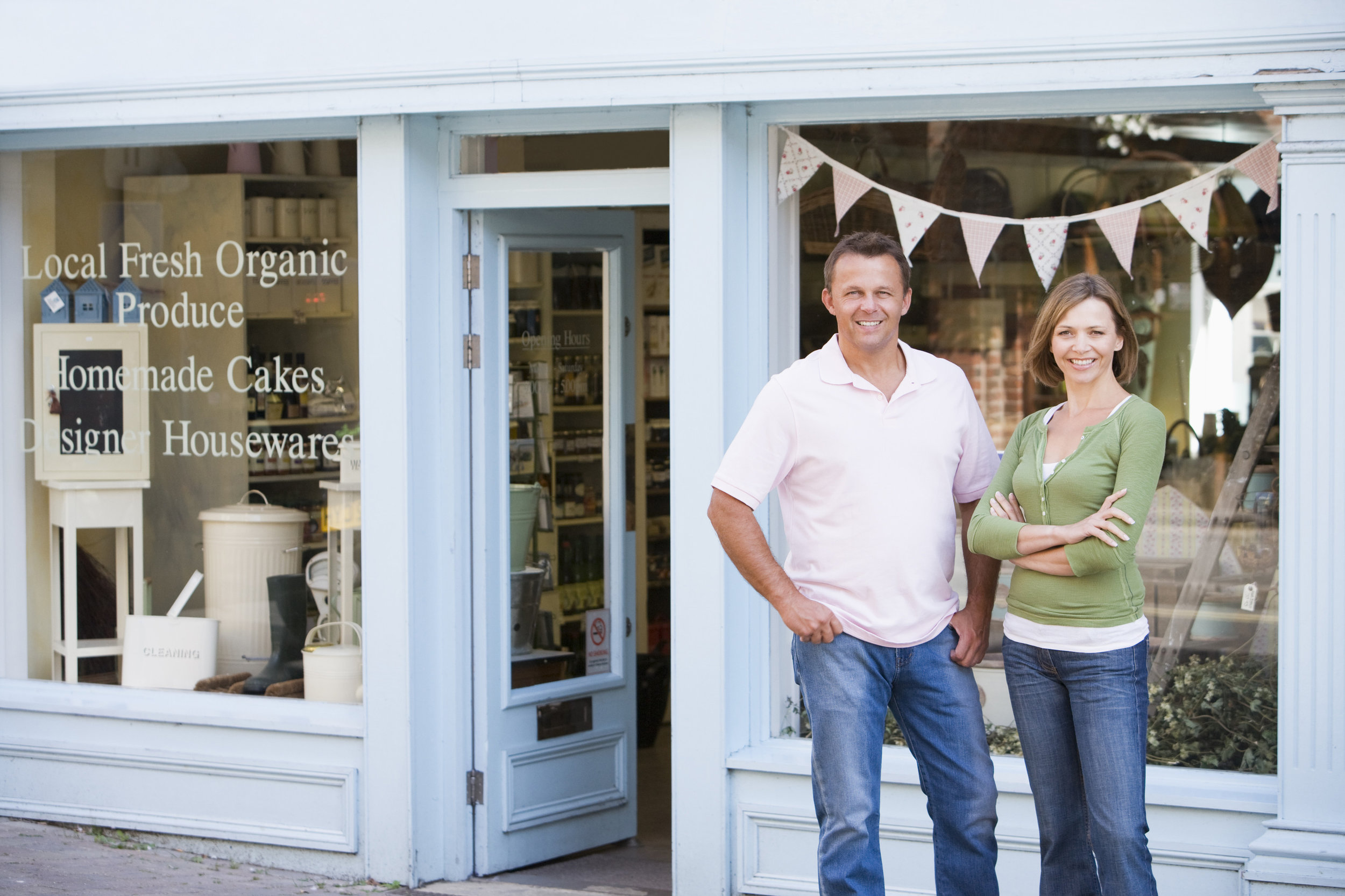 Male and female local business owners standing in front of shop
