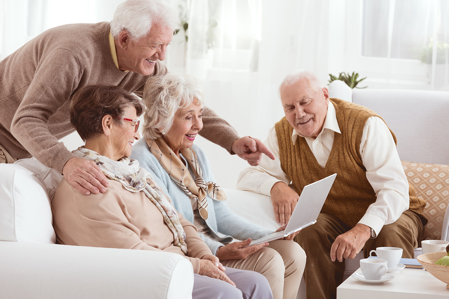 elderly people surrounding a laptop and spreading the word to their friends