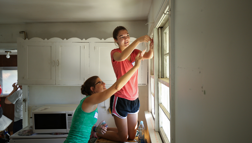 Students apply insulating weatherization strips to prevent heat-loss through windows.