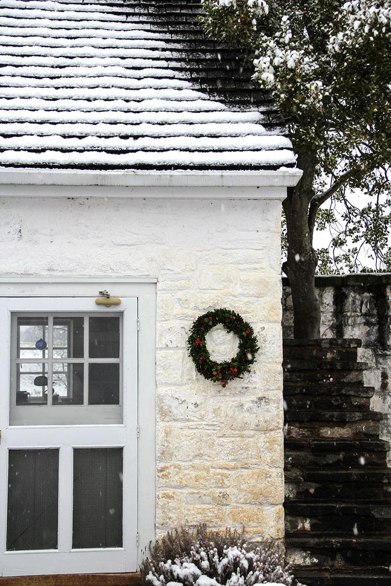 An evergreen wreath adorns a small building at Oak Spring