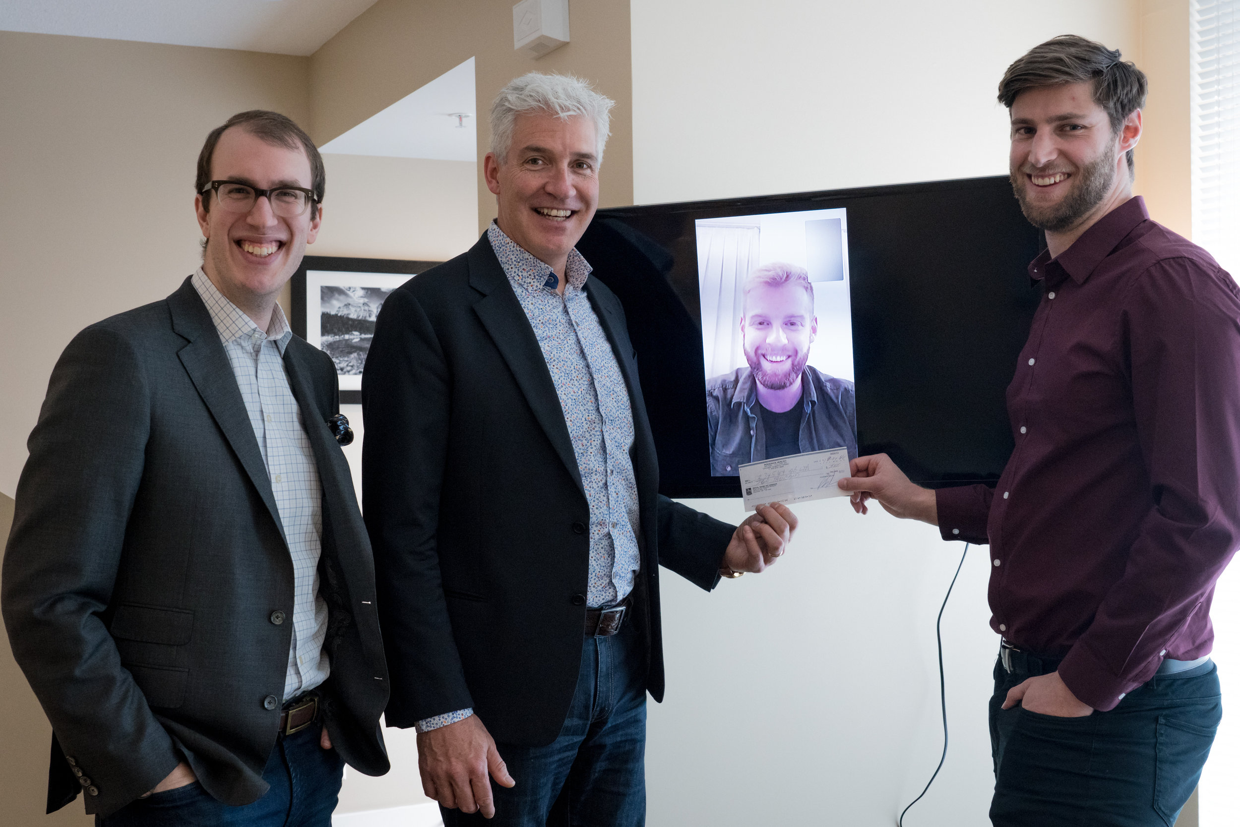 WM Wealth Representatives Mathew McDowell and Rod Walsh (left) with Brett Walsh (screen) and Calgary Premier League Director Jarron Meuller (right).